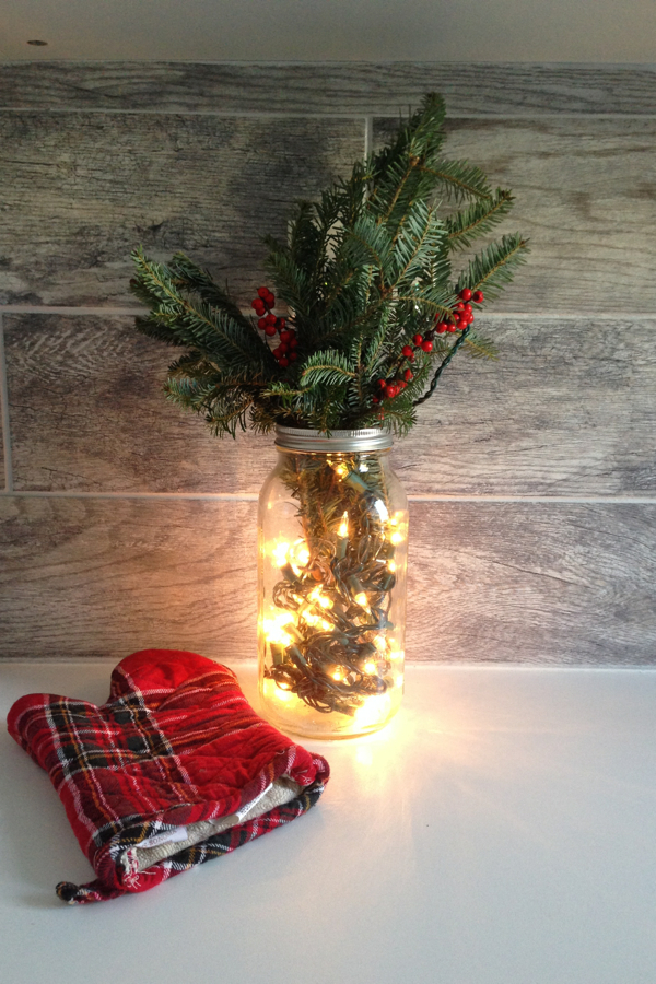 Easy Christmas decor: Mason jar + boughs & berries + strand of Christmas lights