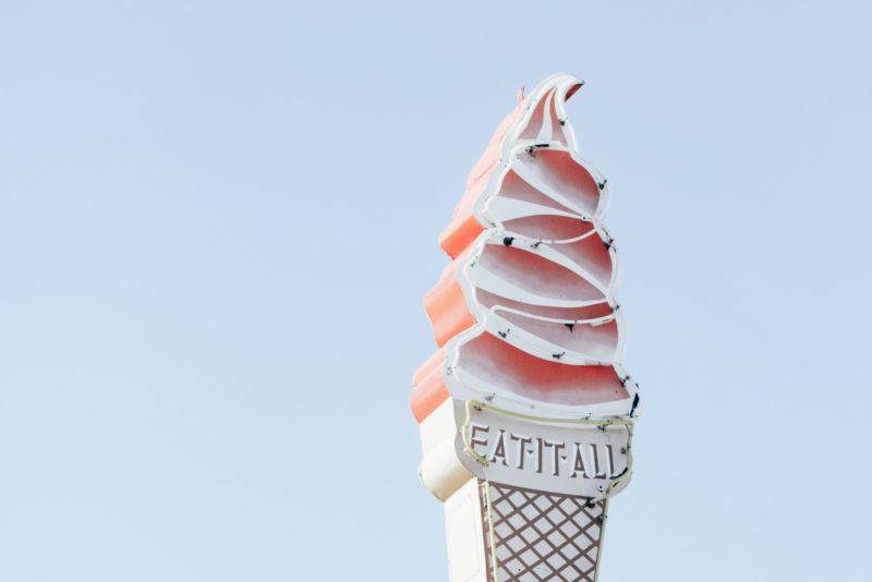 Soft serve ice cream shop sign on light blue sky