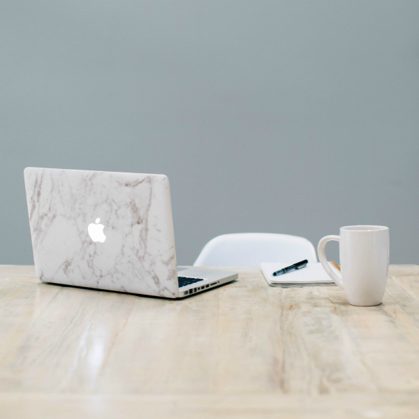 laptop with marble surface decal and white mug on light wood desk in front of gray wall